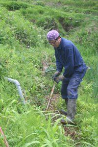 水路を補修する中村さん